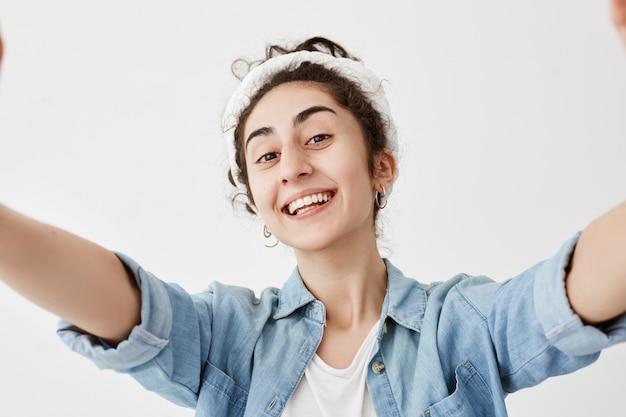 Menina bonito feliz com cabelos escuros e ondulados no bolo que estica os braços, isolados contra a parede branca. na moda feminina, vestida com camisa jeans, sorrindo amplamente.