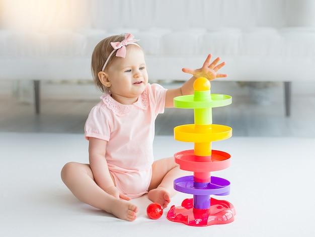 Menina bonito, jogando brinquedo colorido em casa