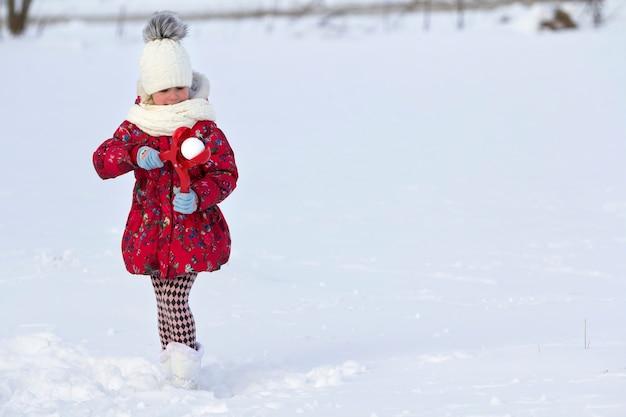 Menina bonito jovem criança desdentada engraçada em roupas quentes, jogando se divertindo fazendo bolas de neve em um dia frio de inverno no fundo branco do espaço da cópia turva brilhante. atividades ao ar livre, jogos de férias.