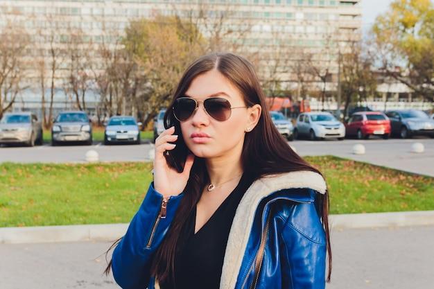 Menina bonito jovem estudante de óculos, falando no telefone móvel no parque.