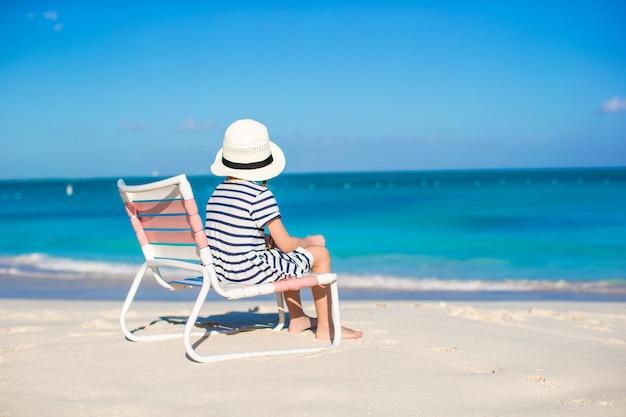 Menina bonito na cadeira de praia relaxar nas férias do caribe