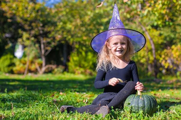 Menina bonito no halloween que traje se divertir ao ar livre