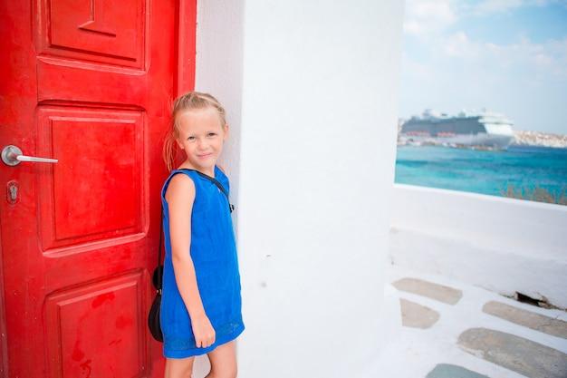 Menina bonito no vestido azul que tem o divertimento ao ar livre perto da igreja. garoto na rua da típica aldeia tradicional grega com paredes brancas e portas coloridas na ilha de mykonos, na grécia