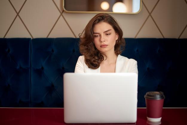 Menina bonito nova que trabalha no portátil no café