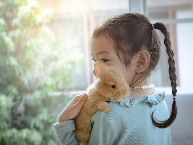 Menina bonito pequena amável que guarda um coelho do marrom do bebê no ombro.