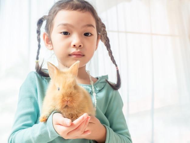 Menina bonito pequena amável que prende um coelho marrom do bebê nas mãos.