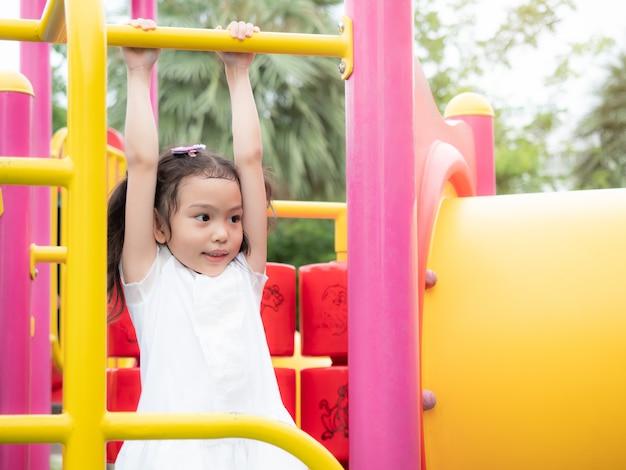Menina bonito pequena asiática feliz que pendura a barra no campo de jogos no parque.