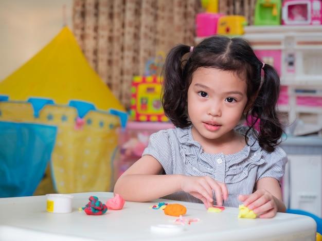 Menina bonito pequena asiática que joga com massa do jogo na tabela branca em casa.