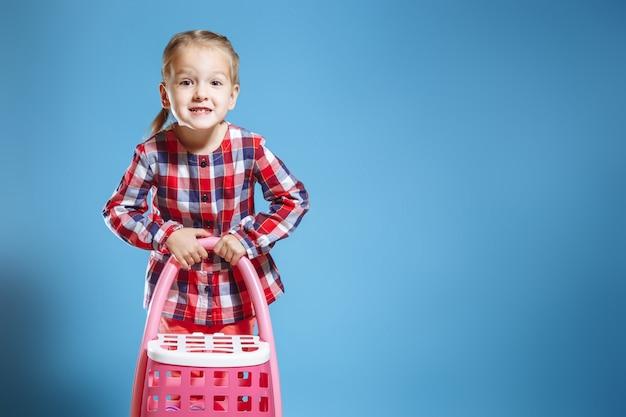 Menina bonito pequena com a mala de viagem do brinquedo no fundo azul.
