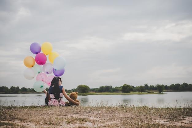 Menina bonito pequena com o urso de peluche que senta-se na grama verde longa fora. menina que prende balões coloridos à disposicão.