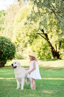 Menina bonito pequena da criança que joga com seu cão-pastor branco grande. foco seletivo