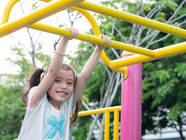 Menina bonito pequena feliz 5-6 anos velha que pendura a barra no campo de jogos.
