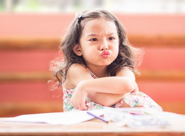 Menina bonito pequena irritada com cruz seu braço quando sua mãe proíbe a observação de desenhos animados e diz-lhe para tirar.