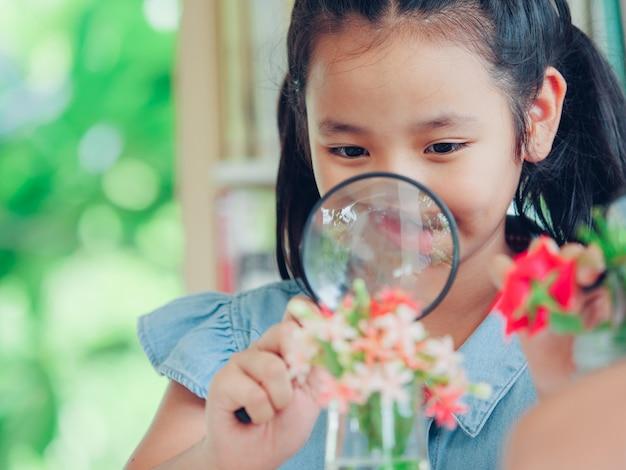 Menina bonito pequena que guarda a lupa nas mãos.