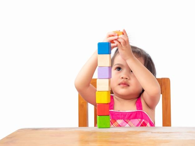 Menina bonito pequena que joga blocos de madeira na tabela. aprendizagem e educação.