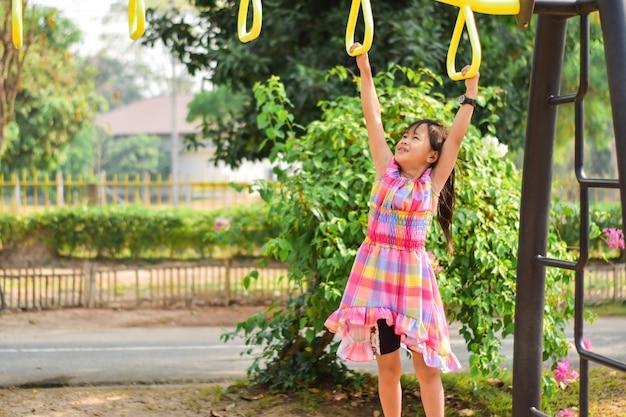 Menina bonito pequena que pendura a barra no parque. treinamento de habilidade de aprendizagem, exercício.