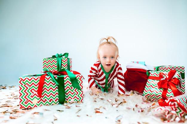 Menina bonito perto de chapéu de papai noel posando sobre fundo de natal. sentado no chão com uma bola de natal. temporada de férias.