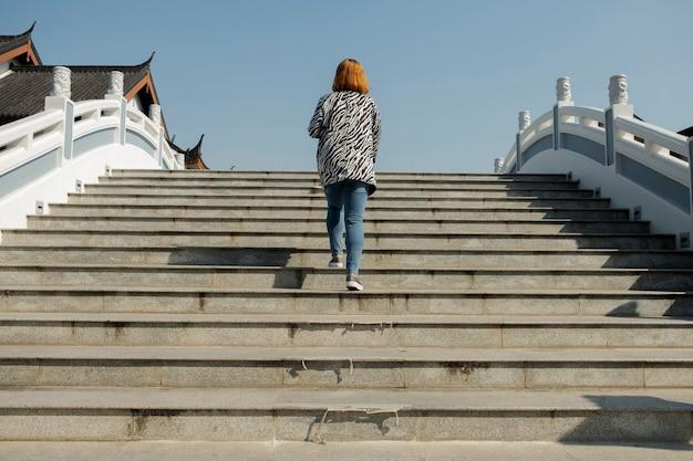 Menina bonito que anda acima das escadas, céu branco brilhante da ponte.