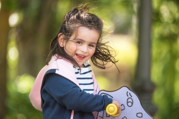 Menina bonito que aprecia no campo de jogos no parque no verão.