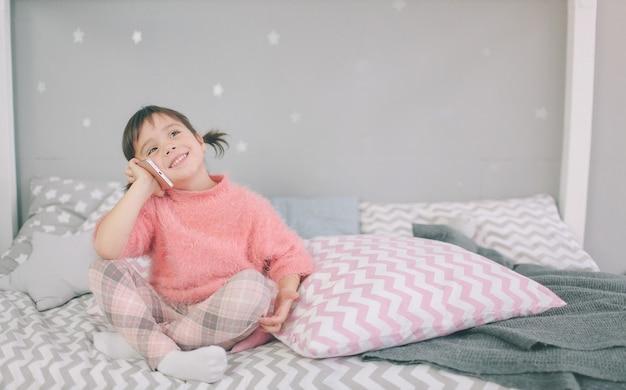 Menina bonito que joga um telefone inteligente, smartphone tem um impacto negativo no desenvolvimento e na saúde mental do seu filho