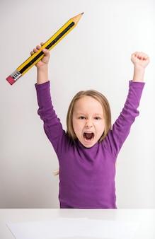 Menina bonito que mantém as mãos com lápis grande.