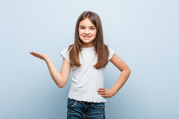 Menina bonito que mostra um espaço da cópia em uma palma e segurando outra mão na cintura.