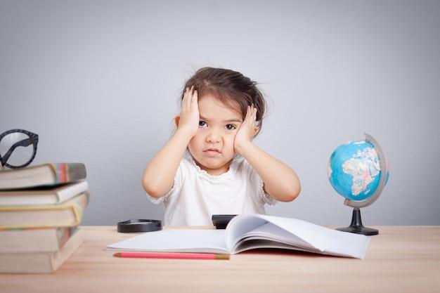 Menina bonito que sofre de dor de cabeça ao fazer o excesso de trabalho com a aprendizagem
