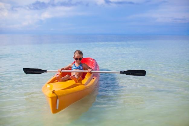 Menina bonito remar um barco no mar azul claro