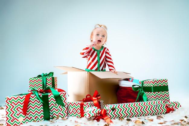 Menina bonito sentado na caixa sobre fundo de natal. feriado, celebração, conceito de criança