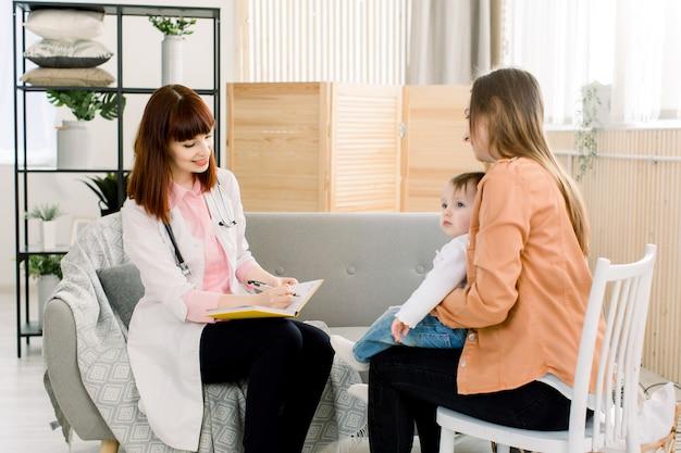 Menina bonito, sentado nas pernas da mãe, quando sua mãe falando com médico feminino