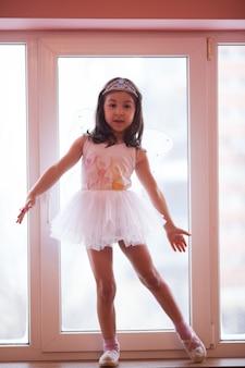 Menina-borboleta em um tutu branco dançando brincando no parapeito da janela
