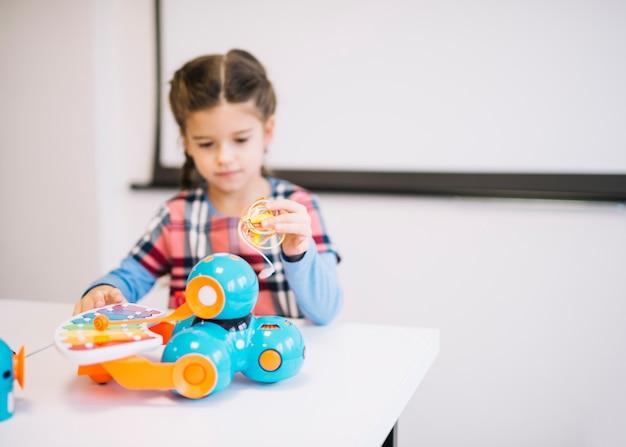 Menina borrada segurando cabos na mão olhando brinquedos elétricos