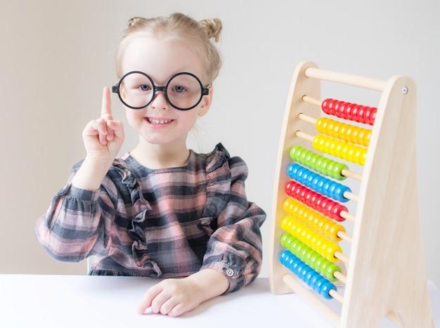 Menina branca com óculos redondos.