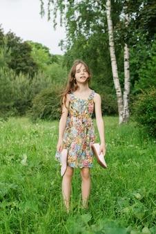 Menina branca de 10 anos em pé na grama e segurando sapatos nas mãos no verão