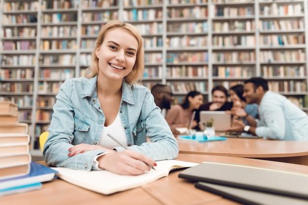 Menina branca de smille que toma notas na biblioteca.