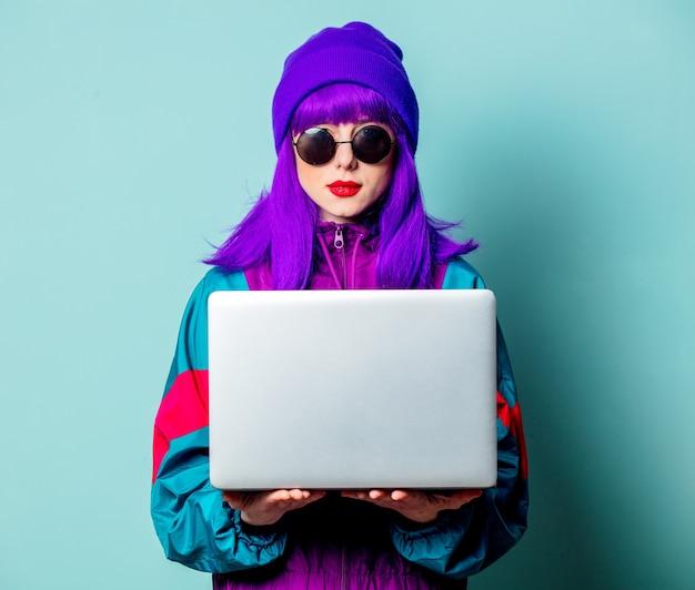 Menina branca elegante com cabelo roxo e agasalho com laptop na parede azul