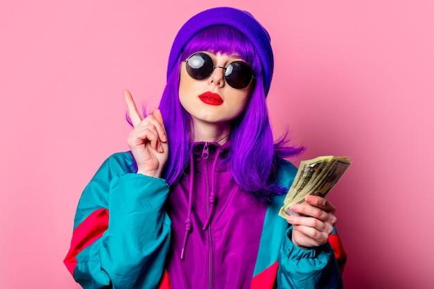 Menina branca elegante com cabelo roxo e agasalho de treino segurando dinheiro na parede rosa