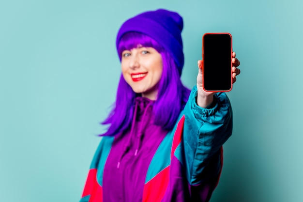 Menina branca elegante com cabelo roxo e agasalho usando o celular na parede azul