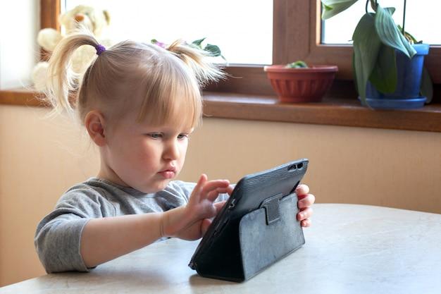 Menina branca em um interior de casa absorto em um jogo em um tablet digital.