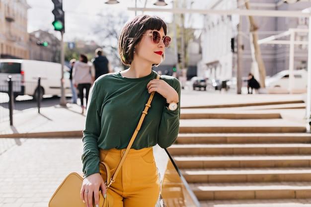 Menina branca pensativa em roupa casual, olhando ao redor da cidade. foto ao ar livre de uma mulher sonhadora em traje verde, de pé na cidade.