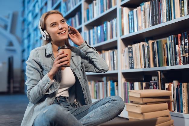Menina branca perto da estante na biblioteca. o aluno está ouvindo música.