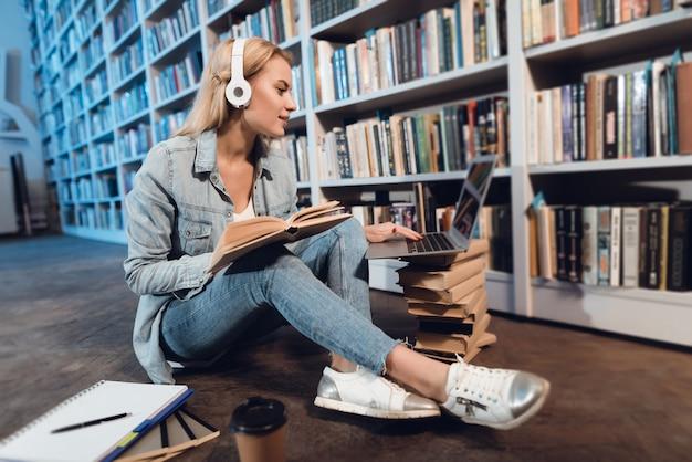 Menina branca que senta-se perto da estante na biblioteca na noite.