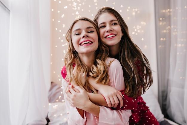 Menina branca sonhadora abraçando a irmã e desviando o olhar com um sorriso. foto interna de amigas arrepiantes posando de pijama.