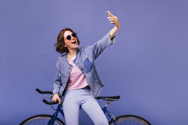 Menina branca sonhadora usando telefone para selfie com bicicleta nova. mulher encaracolada atraente em óculos de sol em pé perto da bicicleta.