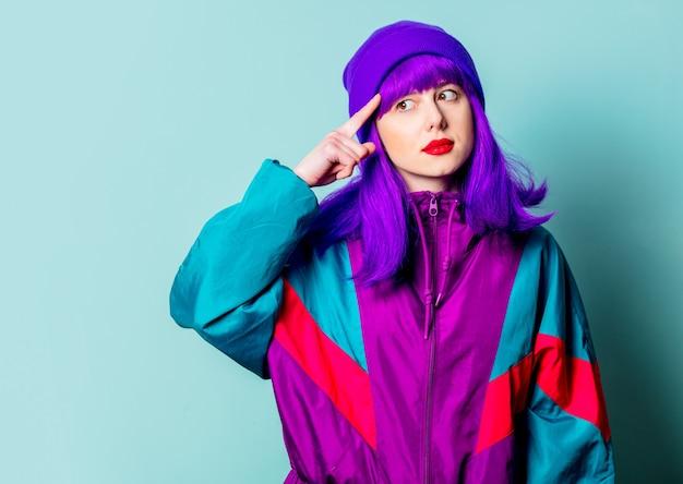 Menina branca surpresa com cabelo roxo e agasalho apontando o dedo na cabeça para uma parede azul