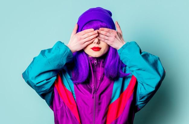 Menina branca surpresa com cabelo roxo e agasalho cobrindo os olhos na parede azul