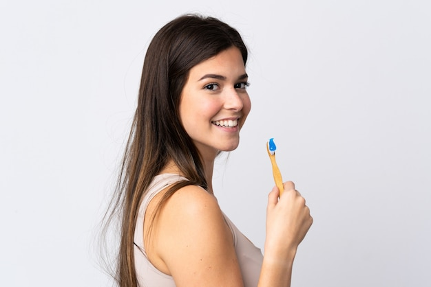 Menina brasileira adolescente escovando os dentes sobre fundo branco isolado