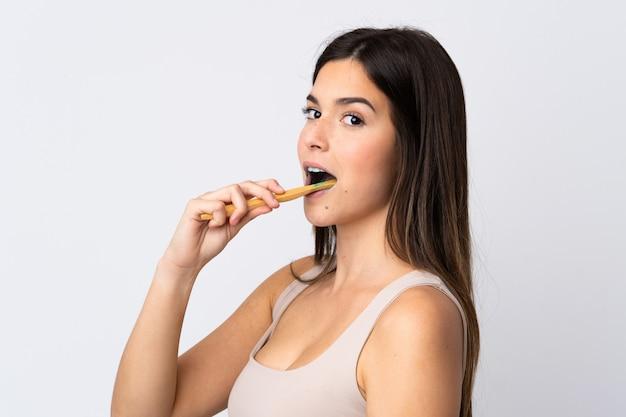 Menina brasileira adolescente escovando os dentes sobre parede branca isolada