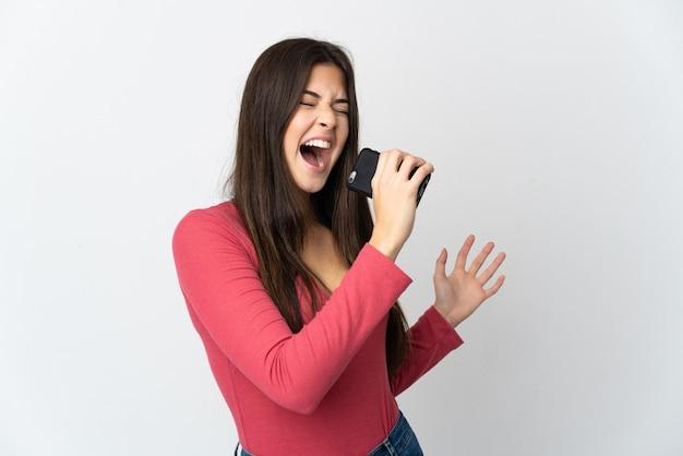 Menina brasileira adolescente isolada em um fundo branco usando telefone celular e cantando