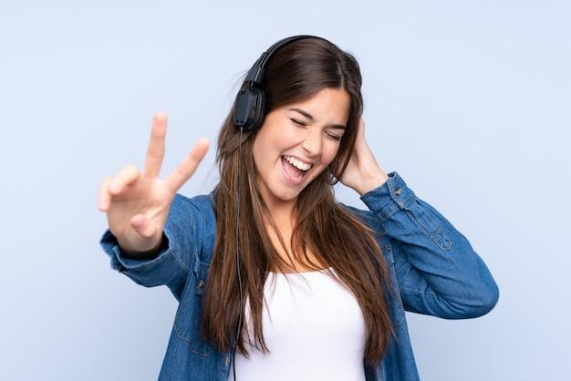 Menina brasileira adolescente ouvindo música e cantando sobre fundo azul isolado